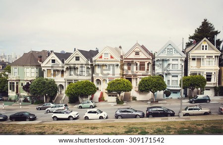 Victorian homes on Steiner Street, view from Alamo Square with the San Francisco skyline behind - stock photo