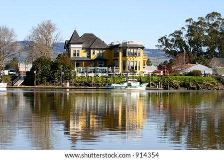 Victorian house on river's edge - stock photo