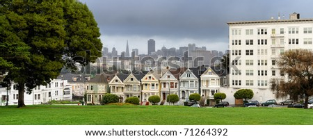 """Victorian houses, known as the """"Painted Ladies"""" with downtown in the background as viewed from Alamo Square in San Francisco, California - stock photo"""