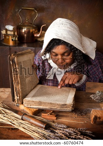 Victorian peasant woman mixing herbs and ingredients in an antique kitchen - stock photo