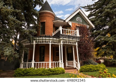 Victorian Queen Anne Style Brick House With White Circular Porch And Tower