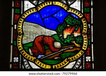 Victorian stained glass window showing Moses and the burning bush.  window over 100 years old, on public display. - stock photo