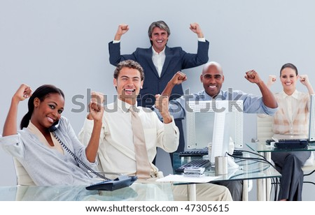 Victorious business team celebrating a success in the office - stock photo