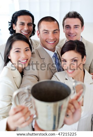 Victorious business team showing their trophy in a company - stock photo