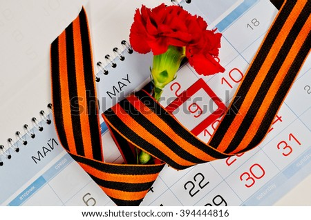 Victory Day card - bright red carnation wrapped with George ribbon lying on the calendar with framed 9th May date. 9 May concept.  - stock photo