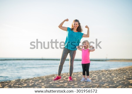 Victory... We both won the race along the water. Well done, Mommy! Well done, Daughter! A happy mother and daughter celebrate their victorious run along the beach at dusk, flexing their arms. - stock photo