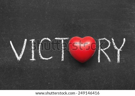 victory word handwritten on blackboard with heart symbol instead of O