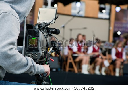 Video camera operator capturing performance on stage - stock photo