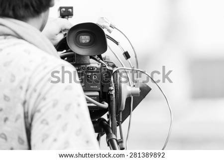 Video camera operator working with his professional equipment - stock photo