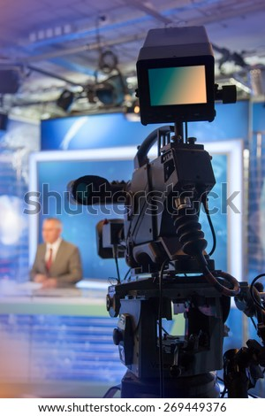 Video camera - recording in TV NEWS studio - Talking To The Camera - stock photo