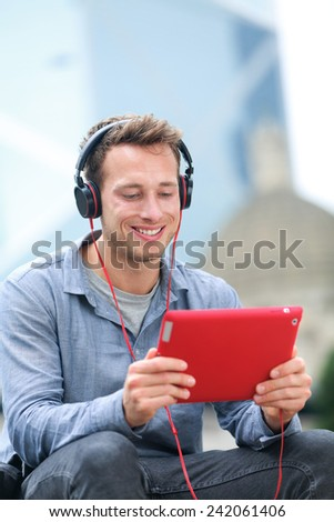 Video chat conversation. Man talking on tablet pc sitting outside using app on 4g wireless device wearing headphones. Casual young urban professional male in his late 20s. - stock photo