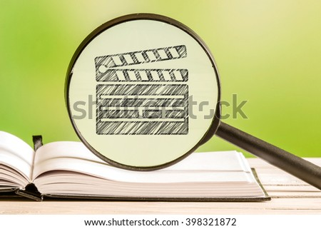 Video collection with a pencil drawing of a clapperboard in a magnifying glass - stock photo