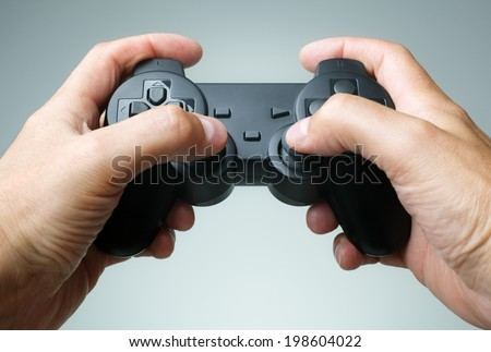 Video game console controller in gamer hands - stock photo