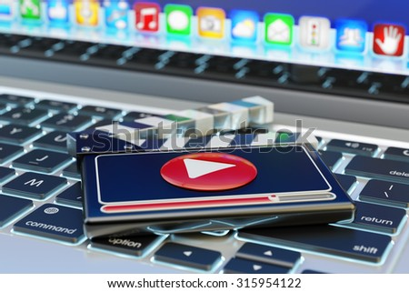 Video media player and online movie concept, film clapper board with play button on computer laptop keyboard - stock photo