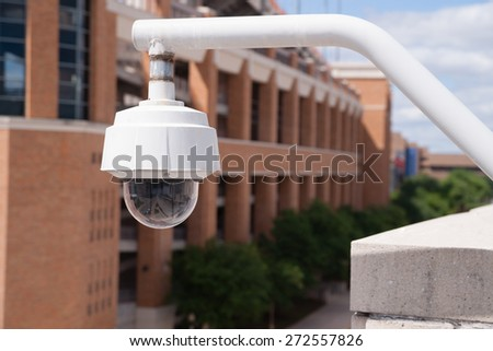 Video Security Camera Housing Mounted High on College Campus - stock photo