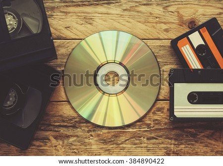 video tapes, audio tapes and compact disc on a wooden table - stock photo