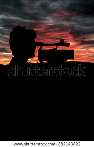 Videographer capturing a scene as sun sets - stock photo
