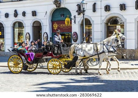 Vienna, Austria - April 24, 2015: City center Street view, people walking and fiaker with white horses in Vienna, Austria - stock photo