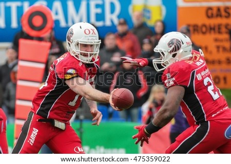 VIENNA, AUSTRIA - April 4, 2016: Grant Enders (New Yorker Lions Braunschweig) hands the ball to David McCants (New Yorker Lions Braunschweig). in a game of the Big Six Football League.