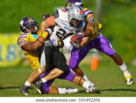 VIENNA, AUSTRIA - APRIL 17 RB Florian Grein (#26 Raiders) is tackled by LB Christopher James (#44 Vikings) and DL Brandon Collier (#99 Vikings) on April 17, 2011 in Vienna, Austria. - stock photo