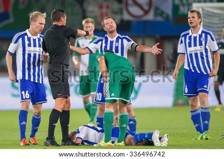 VIENNA, AUSTRIA - AUGUST 28, 2014: Teemu Tainio (#10 Helsinki) argues with Referee Stephane Laurent Lannoy (France) in an UEFA Europa League qualifying game. - stock photo