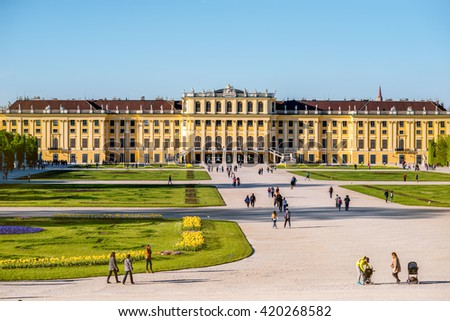 VIENNA, AUSTRIA - CIRCA APRIL 2016: Schonbrunn palace with tourist walk on the alley in Vienna. This Palace is one of the most important architectural and historical monuments in the Austria
