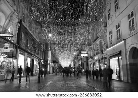 VIENNA, AUSTRIA - December 11, 2009: Vienna -  street at night with tourists and Christmas chandeliers in Vienna, Austria. on December 11, 2009. - stock photo