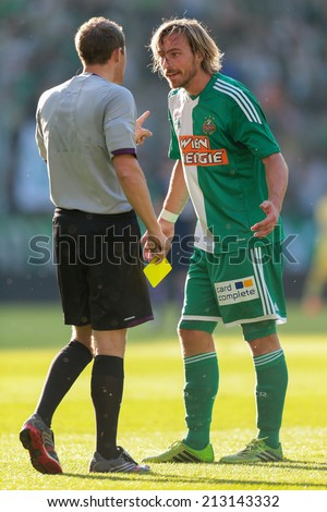 VIENNA, AUSTRIA - JULY 12 Harald Pichler (#27 Rapid) argues with referee Harald Lechner (Austria) at a friendly soccer game on July 12, 2013 in Vienna, Austria. - stock photo