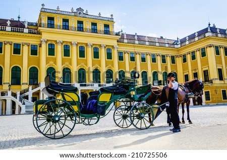 VIENNA, AUSTRIA - JULY17, 2014: Old-fashioned fiacre and a coachman at the Schonbrunn palace in Vienna. - stock photo