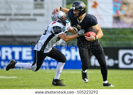 VIENNA, AUSTRIA - JUNE 11 QB Stefan Poster (#88 Rangers) is tackled by DB Andre Pescosta (#48 Raiders) on June 11, 2011 in Vienna, Austria. The Rangers beat the Swarco Raiders II 41:10. - stock photo