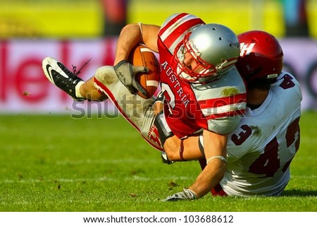 VIENNA, AUSTRIA - JUNE 5 RB Andrej Kliman (#3 Austria) is tackled by DB Bobby Short (#43 Rose Hulman) on June 5, 2011 in Vienna, Austria. Rose Hulman College beats Team Austria 35:34 in overtime. - stock photo