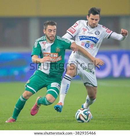 VIENNA, AUSTRIA - OCTOBER 29, 2014: Josip Tadic (#11 Sturm) and Thanos Petsos (#5 Rapid) fight for the ball in an Austrian soccer league game. - stock photo