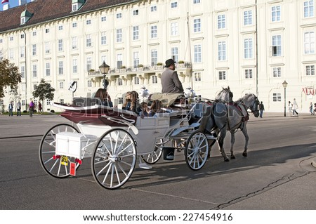VIENNA, AUSTRIA - OCTOBER 09, 2014: Tourists have a ride in the fiaker and pass the Hofburg, Vienna, Austria - stock photo