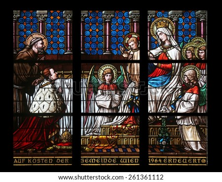 VIENNA, AUSTRIA - OCTOBER 10: Virgin Mary with baby Jesus, angels and Saints, Stained glass in Votiv Kirche (The Votive Church). It is a neo-Gothic church in Vienna, Austria on October 10, 2014 - stock photo