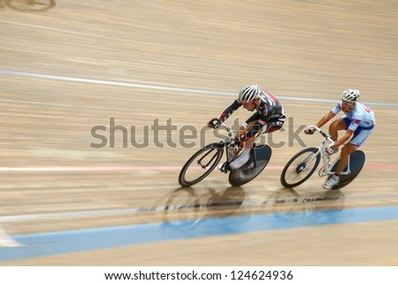 VIENNA,  AUSTRIA - SEPTEMBER 27  Dennis Wauch (Austria) and Filip Taragel (Slovakia) compete and in the men's U23 point race of an indoor cycling meeting on September 27, 2012 in Vienna, Austria. - stock photo
