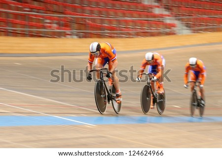 VIENNA,  AUSTRIA - SEPTEMBER 27  Hugo Haag,  Nils Hoenderdaal, and Jeffrey Hoogland (Netherlands) compete in the men's team sprint event of an cycling meeting on September 27, 2012 in Vienna, Austria. - stock photo