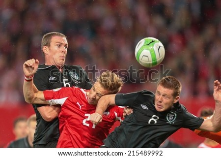 VIENNA, AUSTRIA - SEPTEMBER 10 James McCarthy (#8 IRL), Marc Janko (#21 AUT) and Richard Dunne (#5 IRL) fight for the ball at a World Cup Qualifying game on September 10, 2013 in Vienna, Austria. - stock photo