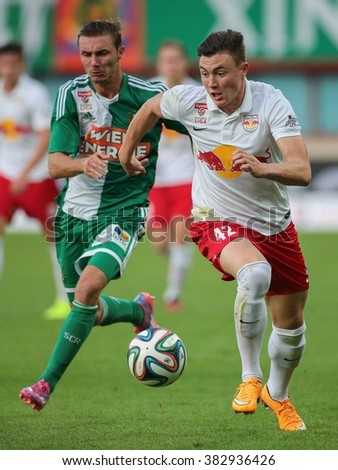 VIENNA, AUSTRIA - SEPTEMBER 28, 2014: Mario Pavelic (#22 Rapid) and Nils Quaschner (#42 Salzburg) fight for the ball in an Austrian soccer league game. - stock photo