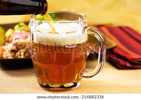 Vienna style smooth amber lager and plate of Bavarian food in background in the spirit of Oktoberfest: sausage, sauerkraut and parsley boiled potatoes.  - stock photo