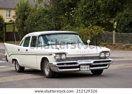 VIERVILLE-SUR-MER, FRANCE - JUNE 4: A vintage Desoto Sportsman drives parallel to Omaha beach on June 4, 2014 in Vierville-sur-mer. Desoto was a US car manufacturer founded in 1928 and closed in 1961 - stock photo