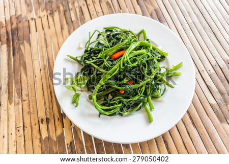 viet nam food - quick fried water spinach with chili and soy sauce on wood background. fired morning glory - stock photo
