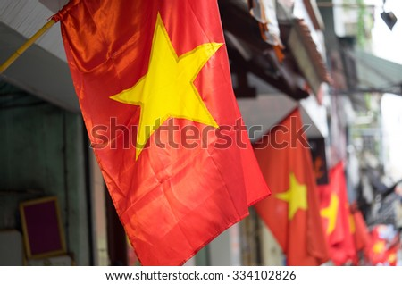 Vietnam flag on a street. Range of red flags and yellow star. - stock photo