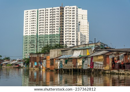 VIETNAM, HO CHI MINH CITY,  OCTOBER 11, 2014: People live in slums which was built above canals in Ho Chi Minh city, the building in the background will be their new home soon. - stock photo