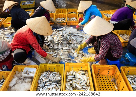 Vietnam women with conical hat are making fish in symmetry position, at Long Hai beach. - stock photo