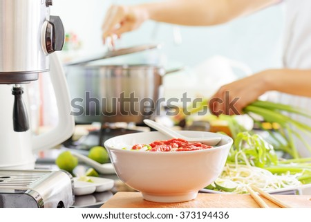 Vietnamese beef noodle soup Pho Bo with garnish of leaves of cilantro, Asian basil and bean sprouts on kitchen table. Young woman is cooking in background. Popular healthy food. - stock photo