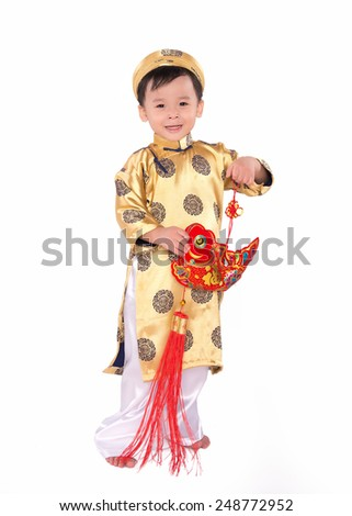 Vietnamese boy cuddling stuffed carp. Portrait of a handsome Asian baby boy on traditional festival costume. Cute little Vietnamese boy in ao dai dress smiling.