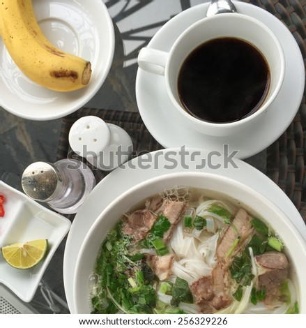 Vietnamese breakfast: coffee, fruits (banana) and Pho (noodle with beef). - stock photo