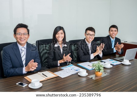 Vietnamese business team applauding and looking at the camera - stock photo