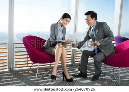 Vietnamese businessman explaining new strategy to his pretty colleague - stock photo