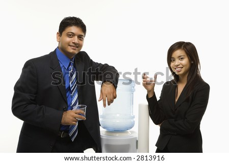 Vietnamese businesswoman and Indian standing at water cooler looking at viewer.